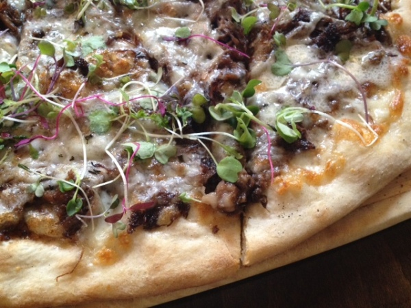 Take a bite out of the Short Rib Pizza, which boasts fig pesto, three cheeses, rosemary, and micro greens